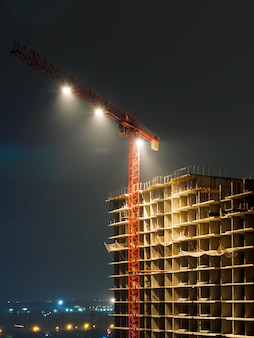 Construction crane and unfinished building at night. bright lights mounted on a crane.