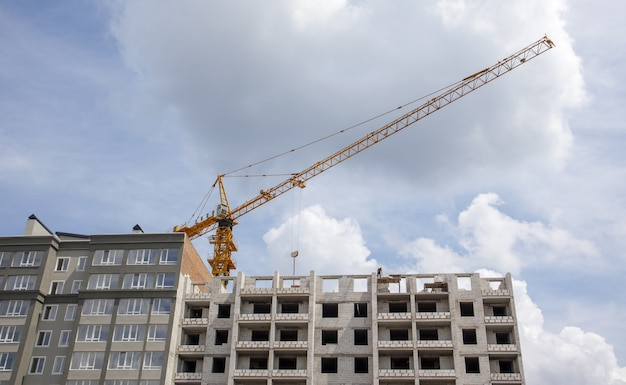 Construction crane on an unfinished residential building against the sun and blue sky. housing construction, apartment building in the city. construction site of residential buildings.