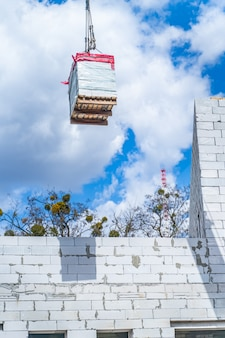 青い空の前にブロックを備えた建設用クレーン。高い住宅の建物を建てる。