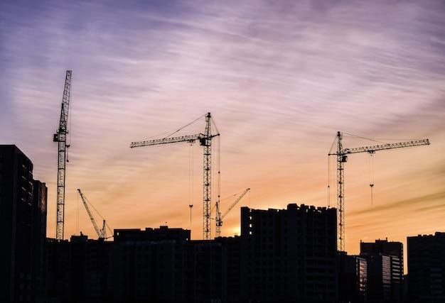 夕日を背景に建物を備えた建設用クレーン。