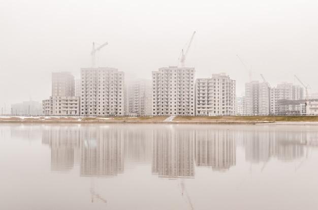 霧の早朝に新しい新しい建物の上に建設用クレーンがあります。