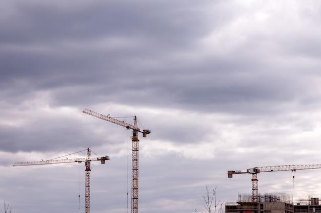 Construction cranes against a cloudy sky