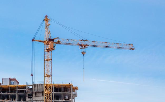 Строительные краны и недостроенный жилой дом против голубого неба. жилищное строительство.