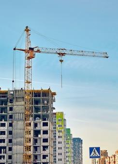 Строительные краны и недостроенный жилой дом против голубого неба. вертикальное изображение.