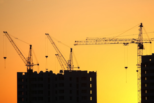 Construction cranes with built houses on the space of the sunset sky