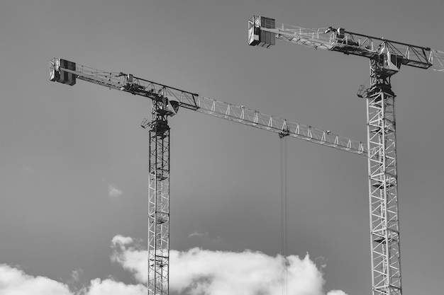 Construction cranes work on creation site against blue sky background. bottom view of industrial crane. concept of construction of apartment buildings and renovation of housing. copy space