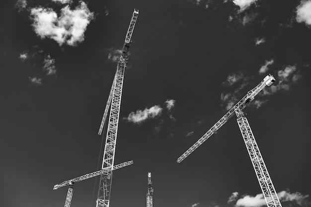 Строительные краны работают на строительной площадке на фоне голубого неба. промышленный кран, вид снизу. концепция строительства многоквартирных домов и ремонта жилья. копировать пространство