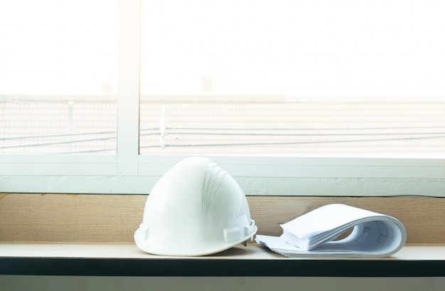 Construction drawing blueprints and white hard hat on table.