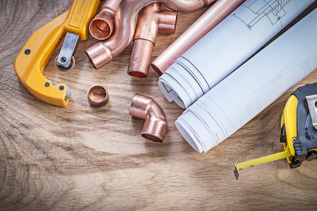 Construction drawings measuring tape copper water pipe cutter fittings on wooden board plumbing concept
