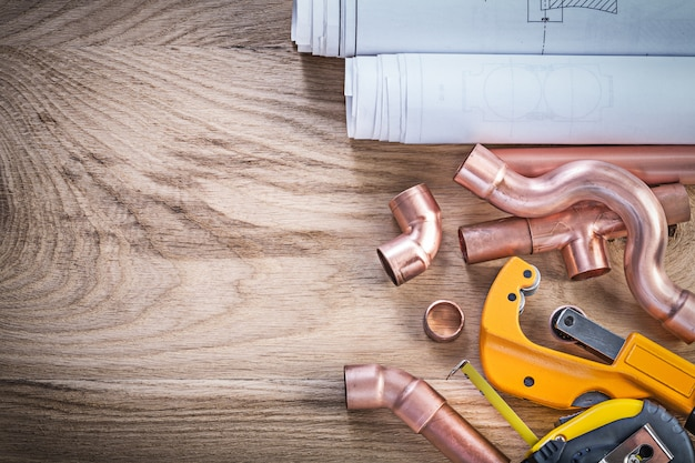 Construction drawings measuring tape water pipe cutter connectors on wood board plumbing concept