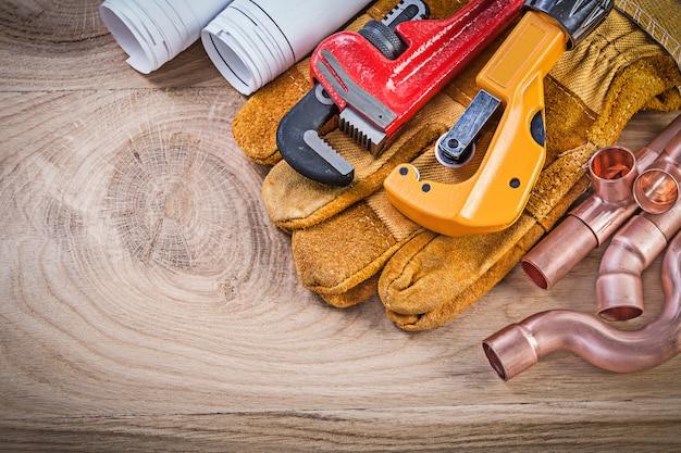 Строительные чертежи защитные перчатки гаечный ключ труборез на деревянной доске сантехника концепции