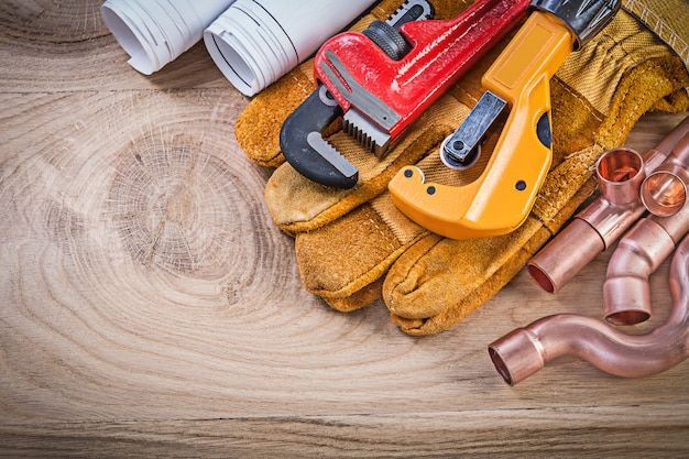 Construction drawings protective gloves monkey wrench pipe cutter fixtures on wooden board plumbing concept