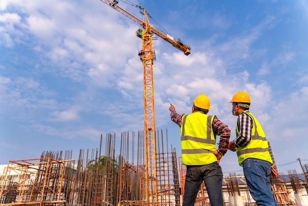 建設技術者と建築家が建設現場で建物の進捗状況を確認します