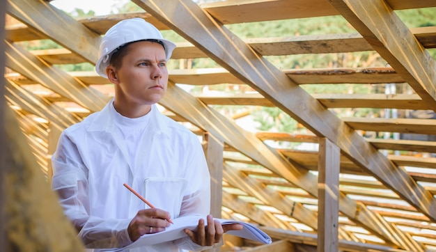 Construction engineer or architect with blueprints on building site of wood frame house. portrait of a man in a white helmet with copy space. foreman in protective clothing. labor day concept.