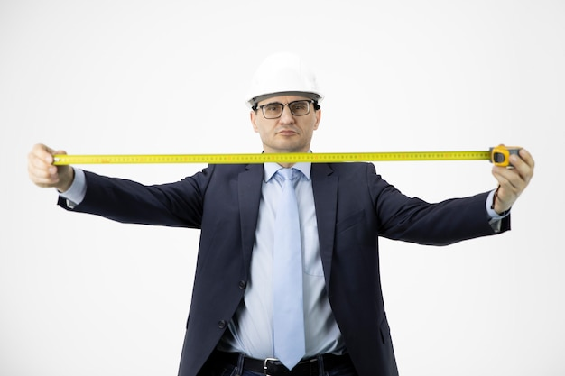 Construction engineer in hard hat holds measuring tape seriously looks at camera