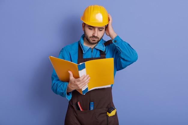 건설 엔지니어는 노란색 종이 폴더를 잡고 새 프로젝트에 대한 정보를 읽고 세부 정보를 이해하지 못합니다.