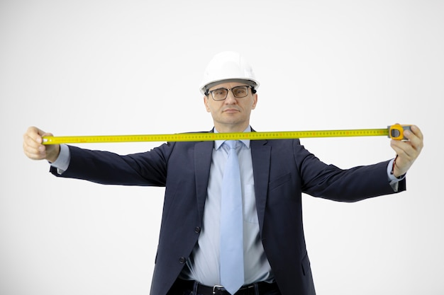 Construction engineer holds measuring tape looks at camera focus on architect
