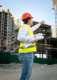 Инженер-строитель в каске и защитной куртке проверяет строительную площадку