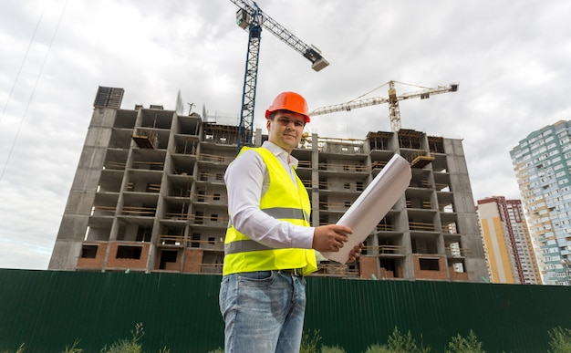 曇りの日に建設現場でヘルメットの建設エンジニア