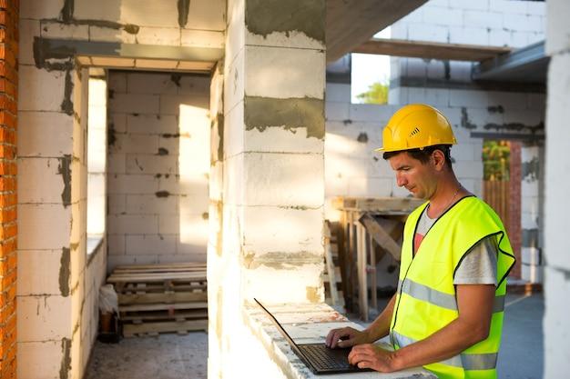 ポーラスコンクリートブロックで作られた家の建設現場の建設エンジニアは、反射型安全ベストとヘルメットのコンピューターで働いています。設計、建設、図面プロジェクト、チェック