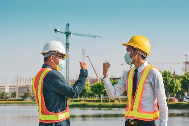 Construction engineer shake hand no touching on building construction site