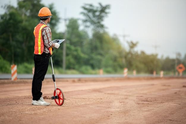 Инженер-строитель наблюдает за работой на строительной площадке