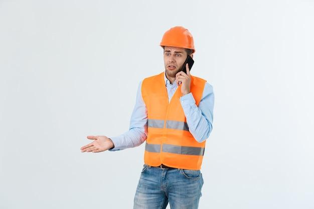 Ingegnere edile che parla al telefono cellulare, persona seria di sesso maschile adulto che utilizza smartphone per la comunicazione con i lavoratori in cantiere.