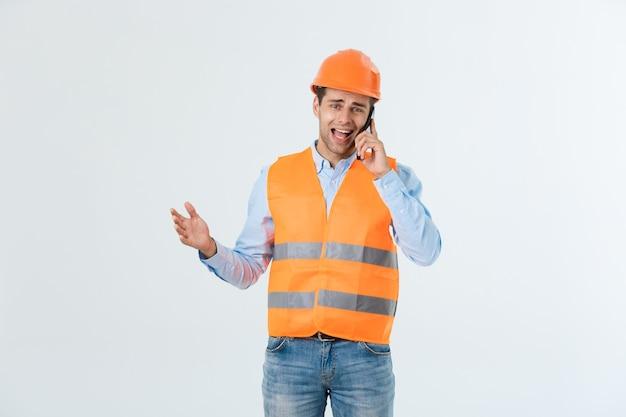 携帯電話で話している建設エンジニア、建設現場の労働者とのコミュニケーションにスマートフォンを使用している深刻な成人男性。