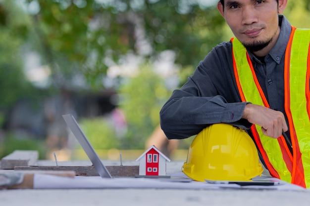 Инженер-строитель с желтой каской безопасностью работает на строительстве