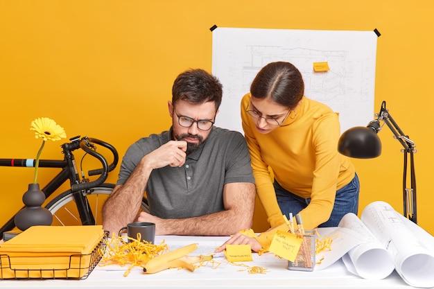 Концепция сотрудничества в строительстве. два молодых архитектора, внимательно сконцентрированные на эскизах, позируют за офисным столом в окружении чертежей и эскизов.
