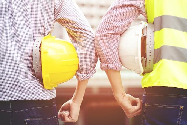 Обсуждение инженеров-строителей с архитекторами на строительной площадке или строительной площадке высотного здания
