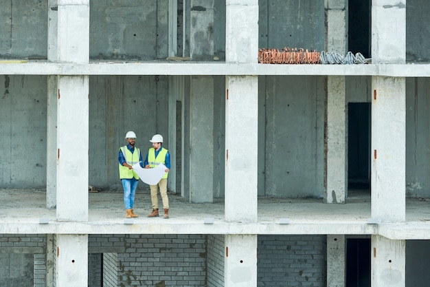 Construction engineers reading draft in unfinished building