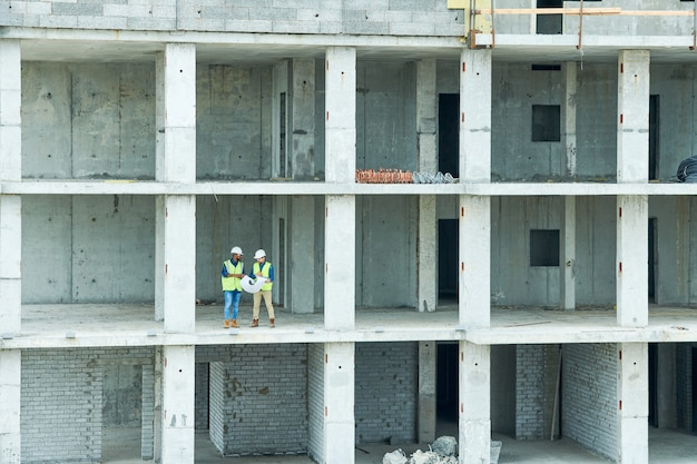 Construction engineers in unfinished building
