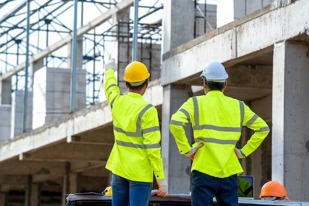 하드 모자를 쓴 건축가와 건설 엔지니어가 건설 현장에서 새로운 프로젝트에 대해 논의합니다.