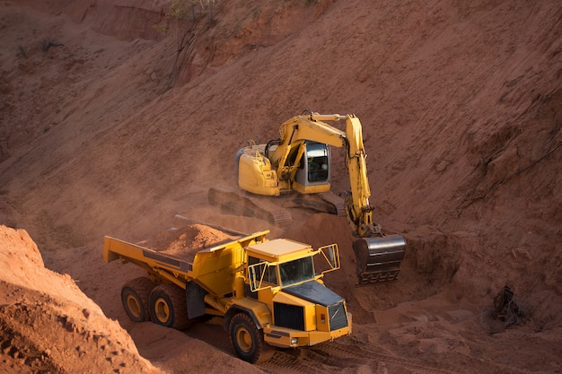 Construction excavator and dump truck digging