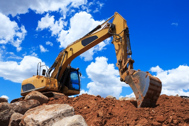 Construction excavator with blue sky and clouds