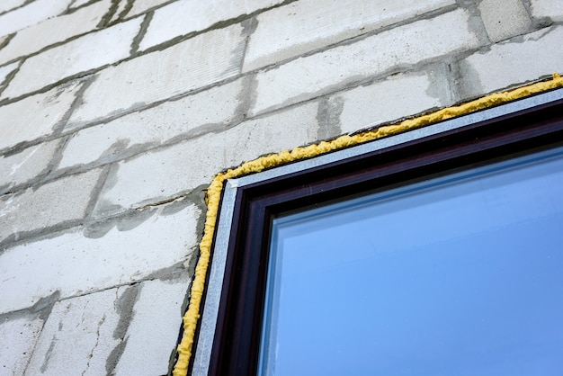 Строительной пеной заделан зазор между пластиковым окном и блочной стеной.