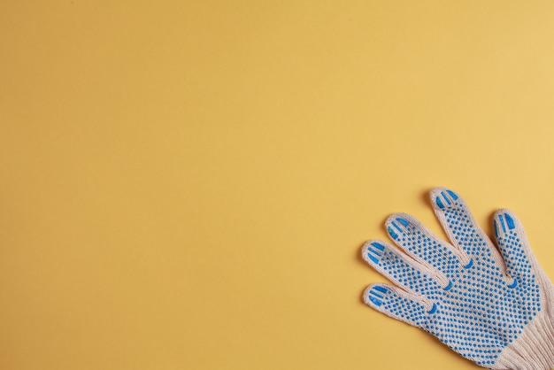 黄色の背景に建設用手袋