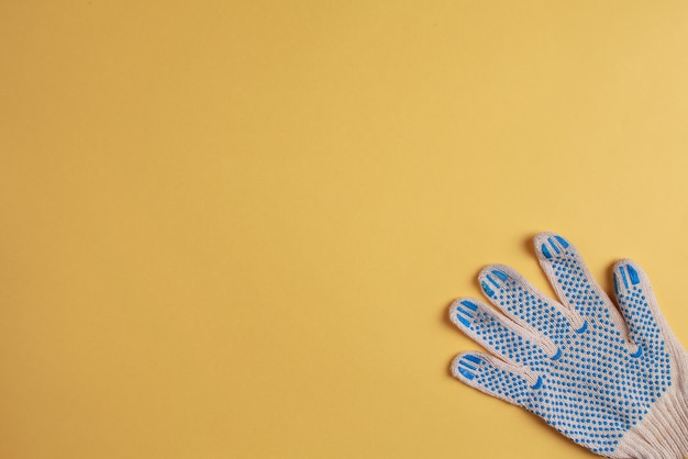 Construction glove on yellow background