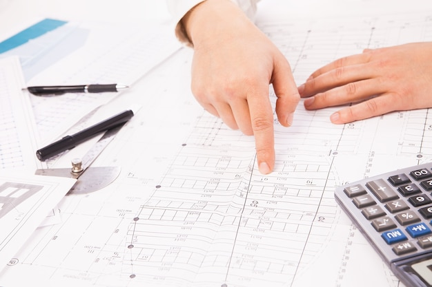 Construction graph on background of businessman hands with pens white