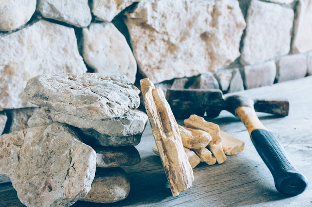 Construction hammer and stack flagstone against the wall of stone closeup.