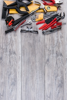Construction hand tools flat lay on wooden background