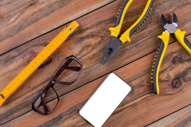 Строительные ручные инструменты на рабочем столе, плоскогубцы, кусачки, линейка