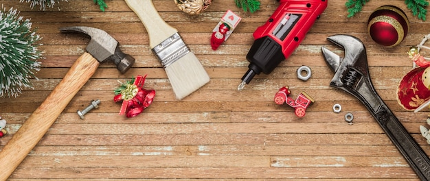 Construction handy tools with christmas ornament on wood