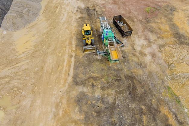건설 중장비가 토지의 등급을 매기고 건설 현장에서 점토 토양 굴착기를 옮기고 있습니다