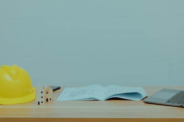 건설 헬멧, 작은 나무 집, 책 및 책상 위의 노트북