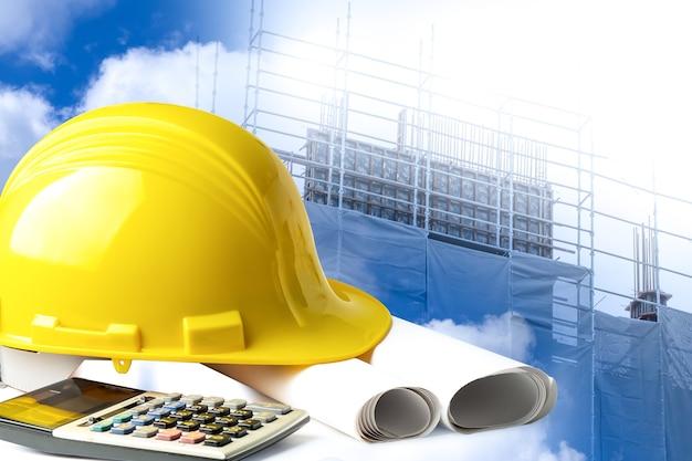현장에서 엔지니어링 작업 프로젝트를 위한 건설 헬멧과 계산기.
