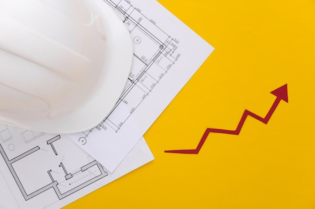 Строительный шлем, планы строительства и стрелка роста, стремящаяся вверх на желтом