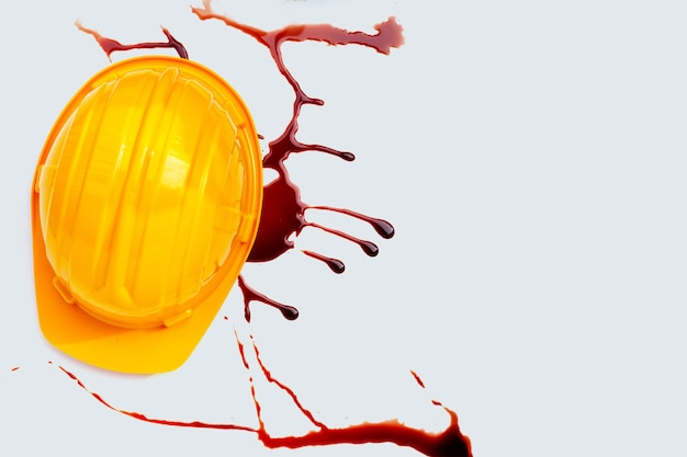 Construction helmet with blood on white background.