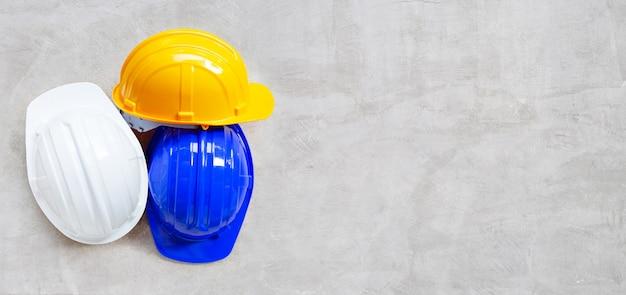 Construction helmets on concrete background.